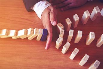 Efekt domino zatrzymany dłonią jako symbol działania zlecenia Stop Loss