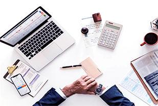 ręce księgowego przy biurku z laptopem, kalendarzem i telefonem