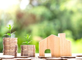 stosy monet i drewniany klocek w kształcie domku